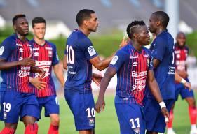 Ronny Rodelin félicité par Prince Oniangué et ses coéquipiers après avoir transformé le penalty offrant la victoire au Stade Malherbe