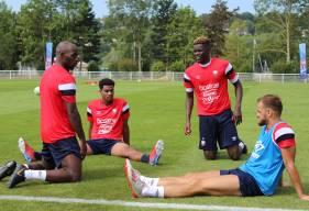 Les défenseurs du Stade Malherbe Caen en séance d'étirements après la séance matinale à Deauville